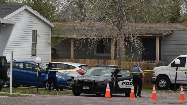 A Colorado Springs police officer goes to help a person who was in a different mobile home to be able to get to her car from behind the crime tape in Colorado Springs, Colo., Sunday, May 9, 2021. A gunman opened fire at a birthday party in Colorado, slaying six adults before killing himself Sunday. (Jerilee Bennett/The Colorado Springs Gazette via AP)