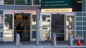 Police tape and evidence markers are seen after a one person was killed during a shooting outside the international departures terminal at Vancouver International Airport, in Richmond, B.C., Sunday, May 9, 2021. THE CANADIAN PRESS/Darryl Dyck