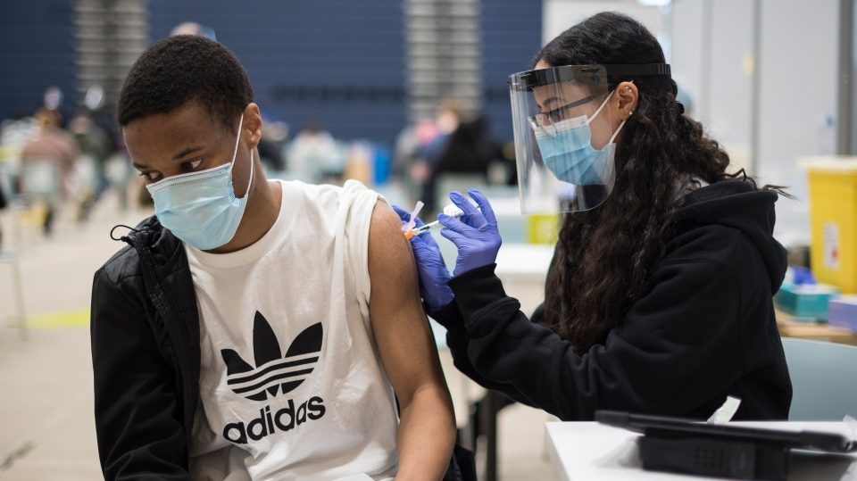 Gina Mikhail administers a vaccine dose to Mathew Derrick-Huie at the COVID-19 vaccination clinic at the University of Toronto campus in Mississauga, Ont., on Thursday, May 6, 2021. THE CANADIAN PRESS/ Tijana Martin