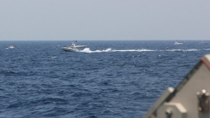 "In this image provided by the U.S. Navy, an Iranian Islamic Revolutionary Guard Corps Navy (IRGCN) fast in-shore attack craft (FIAC), a type of speedboat armed with machine guns, speeds near U.S. naval vessels transiting the Strait of Hormuz, Monday, May 10, 2021. U.S. officials say a group of 13 armed speedboats of Iran's Revolutionary Guard made ""unsafe and unprofessional"" high-speed maneuvers toward U.S. Navy vessels in the Strait of Hormuz on Monday. A U.S. Coast Guard cutter fired warning shots when two of the Iranian boats came dangerously close. (U.S. Navy via AP)"