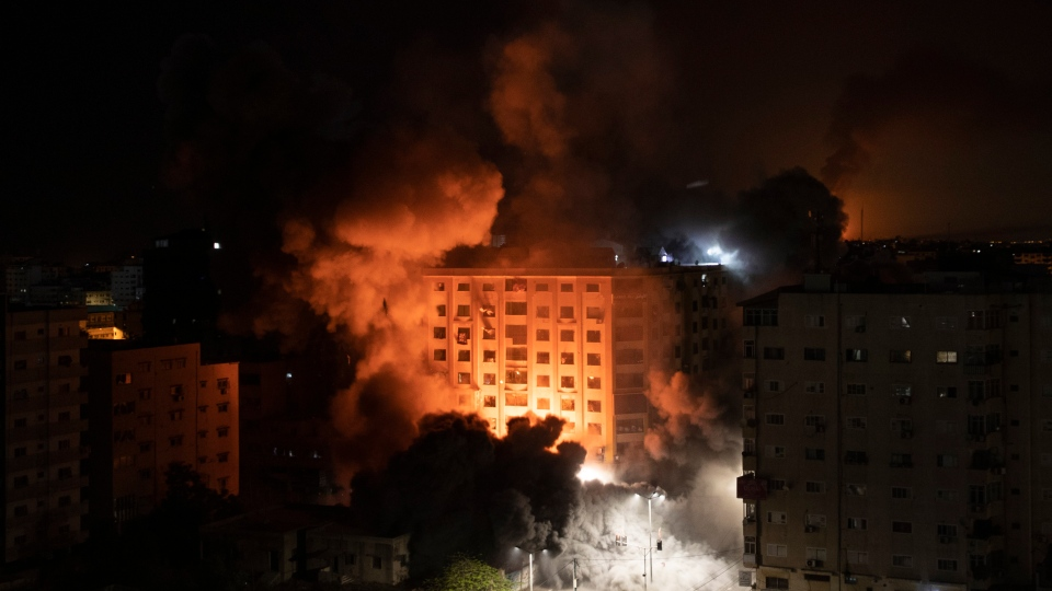 Smoke caused by Israeli airstrikes are seen at a residential building in Gaza City, early Wednesday, May 12, 2021. (AP Photo/Khalil Hamra)
