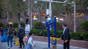 Children play on a playground near security cameras at a public square in Aksu in western China's Xinjiang Uyghur Autonomous Region, Tuesday, April 20, 2021. Xinjiang in far western China had the sharpest known decline in birthrates between 2017 and 2019 of any territory in recent history, according to a new analysis by an Australian think tank. (AP Photo/Mark Schiefelbein)