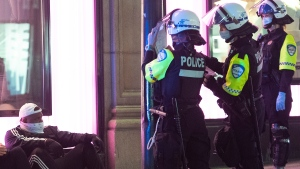 Police issue tickets to people in Montreal, Monday, April 12, 2021, for breaking an 8pm curfew imposed by the Quebec government to help curb the spread of Covid-19 as the COVID-19 pandemic continues in Canada and around the world. THE CANADIAN PRESS/Graham Hughes