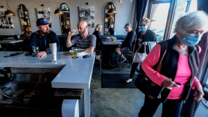 Patrons dine as customers wearing face masks walk into Notorious Burgers restaurant in Carlsbad, Calif., on Friday, Dec. 18, 2020. (AP Photo/Ringo H.W. Chiu)