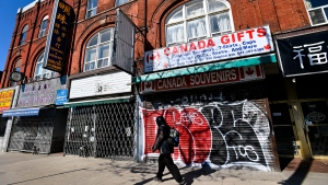 A person walks past closed businesses on Spadina Avenue in Chinatown in Toronto on Thursday, May 13, 2021. THE CANADIAN PRESS/Nathan Denette