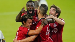 Toronto FC forward Jozy Altidore, center, celebrates after scoring a goal against the Columbus Crew with teammates from left, forward Tsubasa Endoh, defender Omar Gonzalez and forward Patrick Mullins during the second half of an MLS soccer match, Wednesday, May 12, 2021, in Orlando, Fla. (AP Photo/John Raoux)