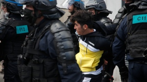 A demonstrator is detained by riot police officers during a banned protest in support of Palestinians in the Gaza Strip, Saturday, May, 15, 2021 in Paris. Marches in support of Palestinians in the Gaza Strip were being held Saturday in a dozen French cities, but the focus was on Paris, where riot police got ready as organizers said they would defy a ban on the protest. (AP Photo/Michel Euler)