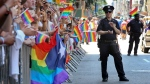 In this Sunday, June 26, 2016, photo, a police officer applauds as parade-goers shout and wave flags during the New York City Pride Parade, in New York City. (AP Photo/Mel Evans)