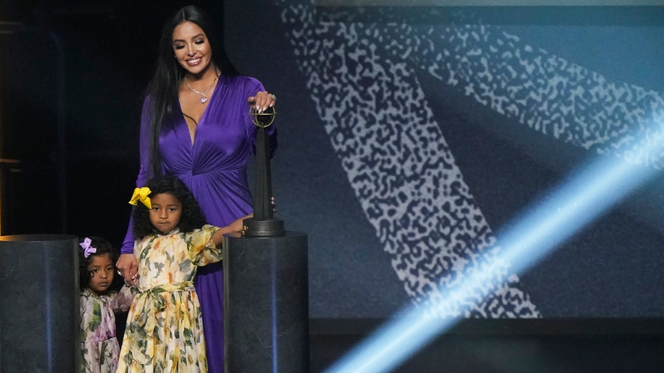 Vanessa Bryant holds hands with her daughters Capri and Bianka as she leaves the stage with her late husband Kobe Bryant's 2020 Basketball Hall of Fame trophy after accepting the award of behalf of him, Saturday, May 15, 2021, in Uncasville, Conn. (AP Photo/Kathy Willens)