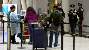 Travellers, who are not affected by new quarantine rules, arrive at Terminal 3 at Pearson Airport in Toronto early Monday, February 22, 2021. Prime Minister Justin Trudeau announced that all travellers entering Canada by air would have to quarantine in a hotel for three days at their own expense starting later today. THE CANADIAN PRESS/Frank Gunn