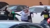 In a screengrab from a video posted to Twitter, a masked man strikes another man near the Toronto bus terminal on May 15, 2021.