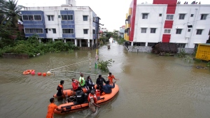 Rescuers help transport people stranded in floodwaters on the outskirts of Chennai, India, Thursday, Nov. 26, 2020. Parts of India's southern coast were flooded Thursday after a cyclone slammed into its shores, triggering heavy rains, uprooting trees and cutting power lines. In Chennai, a coastal city of about 10 million in Tamil Nadu, heavy rains flooded streets, knocked down trees and cut power for several hours. Many residential areas were flooded and people remained indoors. (AP Photo/R. Parthibhan)