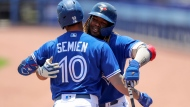 Toronto Blue Jays' Vladimir Guerrero Jr., right, congratulates Marcus Semien on his home run against the Philadelphia Phillies during the first inning of a baseball game Sunday, May 16, 2021, in Dunedin, Fla. (AP Photo/Mike Carlson)