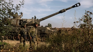 Two Israeli soldiers walk around an artillery unit, at the Israeli Gaza border, Sunday, May 16, 2021. (AP Photo/Heidi Levine)