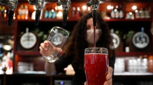 The first alcoholic drinks are poured for customers: two pints of cider at the Shakespeare's Head pub, which will be reopening for the first time to serve indoor customers since the end of the latest coronavirus lockdown, in London, Monday, May 17, 2021. (AP Photo/Alastair Grant)