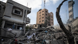 The remains of a six-story building destroyed by an early morning Israeli airstrike are seen in Gaza City, Tuesday, May 18, 2021. Israel carried out a wave of airstrikes on what it said were militant targets in Gaza, leveling a six-story building in downtown Gaza City, and Palestinian militants fired dozens of rockets into Israel early Tuesday, the latest in the fourth war between the two sides, now in its second week. (AP Photo/Khalil Hamra)