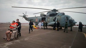 This photograph provided by Indian navy shows, one of the men rescued by the navy from the Arabian sea being brought for medical attention at naval air station INS Shikra in Mumbai, India, Tuesday, May 18, 2021. The Indian navy is working to rescue crew members from a sunken barge and a second cargo vessel that was adrift Tuesday off the coast of Mumbai after Cyclone Tauktae, struck the western coast. (Indian Navy via AP)