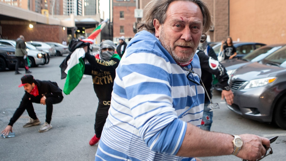 A pro-Israel supporter flees during a brawl with pro-Palestine supporters following a demonstration against the current violence in Gaza in Toronto on Saturday, May 15, 2021. THE CANADIAN PRESS/Chris Young