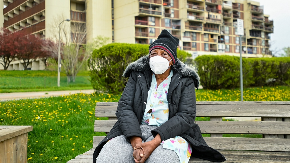 An elderly woman rests on a bench in a neighbourhood that Ontario has designated a postal code hotspot during the COVID-19 pandemic in Toronto on Monday, May 3, 2021. THE CANADIAN PRESS/Nathan Denette