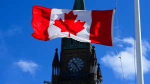 The House of Commons returns today to sit for five weeks following the Easter break. A Canada flag is pictured with the Peace Tower on Parliament Hill in Ottawa on Monday, April 12, 2021. THE CANADIAN PRESS/Sean Kilpatrick