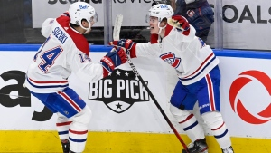 Montreal Canadiens centre Nick Suzuki (14) celebrates his game winning goal against the Toronto Maple Leafs with teammate Cole Caufield (22) during overtime NHL Stanley Cup playoff action in Toronto on Thursday, May 27, 2021. THE CANADIAN PRESS/Frank Gunn