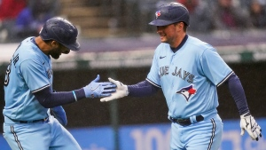Toronto Blue Jays' Joe Panik, right, is congratulated by Lourdes Gurriel Jr. after Panik hit a two-run home run during the third inning of the team's baseball game against the Cleveland Indians, Friday, May 28, 2021, in Cleveland. (AP Photo/Tony Dejak)