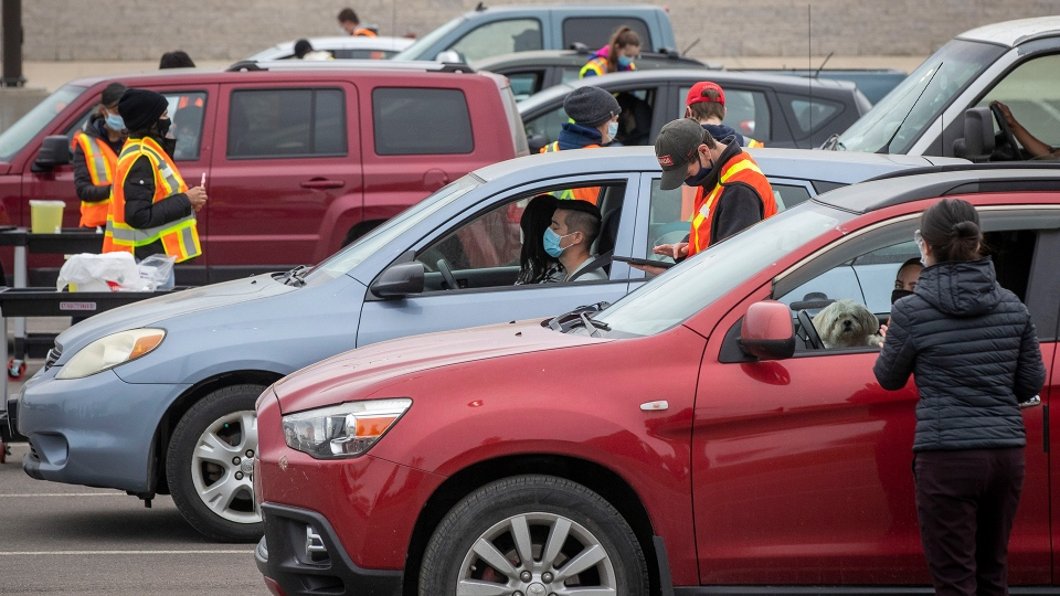 People sit in their vehicles while they wait to receive a COVID-19 vaccine at a drive-thru clinic at Richardson Stadium in Kingston, Ont., on Friday, May 28, 2021. THE CANADIAN PRESS/Lars Hagberg