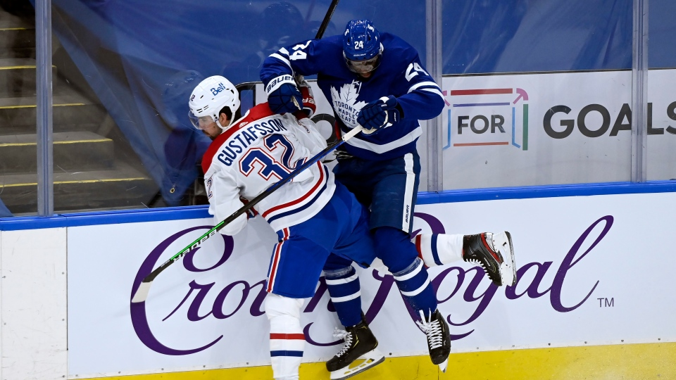 Montreal Canadiens defenceman Erik Gustafsson (32) checks Toronto Maple Leafs forward Wayne Simmonds (24) during first period NHL Stanley Cup hockey action in Toronto, Monday, May 31, 2021. THE CANADIAN PRESS/Nathan Denette