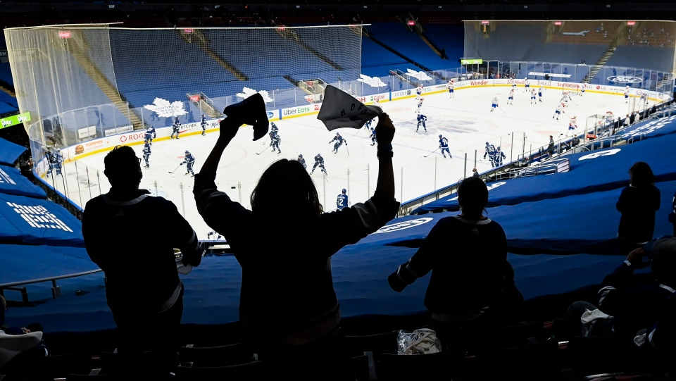 Health-Care workers cheers before the Toronto Maple Leafs play against the Montreal Canadiens during first period game seven NHL Stanley Cup playoff hockey action in Toronto on Monday, May 31, 2021. THE CANADIAN PRESS/Nathan Denette