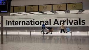 FILE - In this Tuesday, Jan. 26, 2021 file photo, arriving passengers walk past a sign in the arrivals area at Heathrow Airport in London.(AP Photo/Matt Dunham, File)