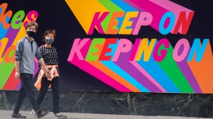 A couple walk past an inspirational mural in Toronto on Tuesday May 25, 2021. THE CANADIAN PRESS/Frank Gunn