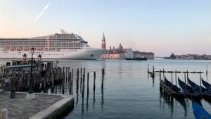 Cruise ship MSC Orchestra passes in the Giudecca Canal in Venice, Italy, early Thursday, June 3, 2021. Early risers in Venice woke Thursday to the sight of a cruise ship traveling down the Giudecca canal for the first time since the pandemic, despite pledges by subsequent Italian governments to reroute the huge vessels due to safety and environmental concerns. (JC Viens via AP)