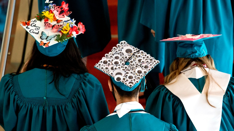 Graduates head towards a staircase for a group photo before the start of their graduation ceremony Thursday, May 27, 2021, in Texas. (Jacob Ford/Odessa American via AP)