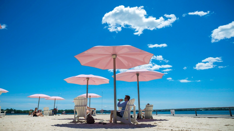 People enjoy the warm weather while protecting themselves from the sun with the pink umbrellas at Sugar Beach, in Toronto on Friday, July 6, 2018. THE CANADIAN PRESS/Tijana Martin