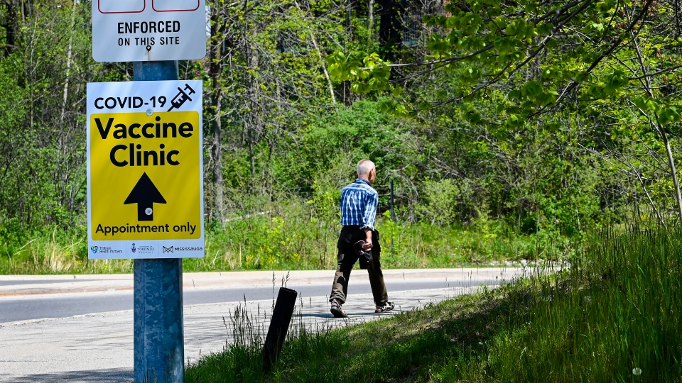 A man makes his way past signage to a mass COVID-19 vaccination centre at the University of Toronto's Mississauga campus during the COVID-19 pandemic in Mississauga, Ont., on Monday, May 17, 2021. Starting tomorrow every resident aged 18-plus will be able to book their vaccine appointment in Ontario. THE CANADIAN PRESS/Nathan Denette