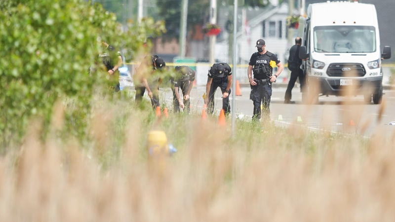 A line of police officers look for evidence at the scene of a car crash in London, Ontario on Monday, June 7, 2021. Police in London, Ont., say four people have died after several pedestrians were struck by a car Sunday night. THE CANADIAN PRESS/Geoff Robins