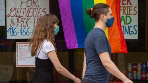 A pride flag hangs in a restaurant window as a masked man and woman walk past on Saturday, June 6, 2020. Pride month's economic impact will be muted due to COVID-19 restrictions. THE CANADIAN PRESS/Frank Gunn