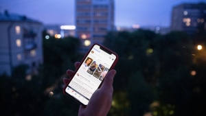 A user holds a smartphone with an opened Facebook page in Moscow, Russia, Thursday, June 10, 2021. Russian authorities have ordered Facebook and messaging app Telegram to pay steep fines for failing to remove banned content. The move could be part of growing Russian efforts to tighten control over social media platforms. (AP Photo/Pavel Golovkin)
