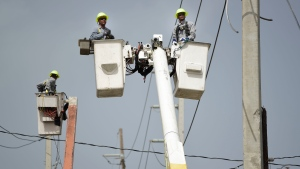 FILE - In this Oct. 19, 2017 file photo, Puerto Rico Electric Power Authority workers repair distribution lines damaged by Hurricane Maria in the Cantera community of San Juan, Puerto Rico. Luma, the private company that took over power transmission and distribution in June 2021 has struggled with widespread outages, affecting more than 1 million customers so far in its first two weeks, triggering several mayors to declare a state of emergency and distribute ice and generators.(AP Photo/Carlos Giusti, File)
