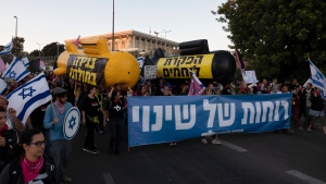"""Israeli protesters march during a demonstration against Israeli Prime Minister Benjamin Netanyahu outside the Knesset, Israel's parliament in Jerusalem, Saturday, June 5, 2021. Hebrew on the banner reads: """"Winds of change."""" (AP Photo/Sebastian Scheiner)"""