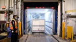 A FedEx worker loads the 255,600 doses of the Moderna COVID‑19 vaccine which came from Europe into a freezer trailer to be transported during the COVID-19 pandemic at Pearson International Airport in Toronto on Wednesday, March 24, 2021. THE CANADIAN PRESS/Nathan Denette
