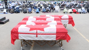 Mourners pray as caskets draped in Canadian flags are lined up at a funeral for the four Muslim family members killed in a deadly vehicle attack, at the Islamic Centre of Southwest Ontario in London, Ont., on Saturday, June 12, 2021. Talat Afzaal, 74, her son Salman Afzaal, 46, his wife Madiha Salman, 44, and their 15-year-old daughter Yumna Salman all died last Sunday night while out for a walk after a man in a truck drove them down in what police have called a premeditated attack because they were Muslim. THE CANADIAN PRESS/Nathan Denette-Pool