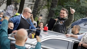 Brazil's President Jair Bolsonaro flashes a thumbs up as he arrives to take part in caravan of motorcycle enthusiasts in a show of support for Bolsonaro, in Sao Paulo, Brazil, Saturday, June 12, 2021. (AP Photo/Marcelo Chello)
