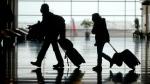 FILE - In this Tuesday, March 9, 2021 file photo, travelers walk through the Salt Lake City International Airport, in Salt Lake City. (AP Photo/Rick Bowmer, File)