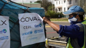 Airport workers spray the cargo of Covax COVID-19 vaccines on arrival in Antananarivo, Madagascar, Saturday May 8, 2021. The president had previously promoted the use of a local traditional remedy known as Covid-Organics to combat coronavirus.(AP Photo/Alexander Joe)