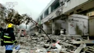 In this image taken from a video footage run by China's CCTV, a firefighter walks near the aftermath of a gas explosion in Shiyan city in central China's Hubei Province on Sunday, June 13, 2021. At least a dozen people were killed and more seriously injured Sunday after a gas line explosion tore through the residential neighborhood in central China. (CCTV via AP Video)