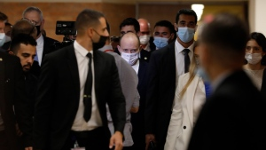 Naftali Bennett, center, who is set to become Prime Minister, is surrounded by bodyguards at the Israel's parliament, known as the Knesset, prior to the vote on the new government, in Jerusalem, Sunday, June 13, 2021. Israel is set to swear in a new government on Sunday that will send Prime Minister Benjamin Netanyahu into the opposition after a record 12 years in office and a political crisis that sparked four elections in two years. (AP Photo/Ariel Schalit)