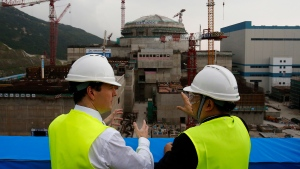 """In this Oct. 17, 2013, file photo, then British Chancellor of the Exchequer George Osborne, left, chats with Taishan Nuclear Power Joint Venture Co. Ltd. General Manager Guo Liming as he inspects a nuclear reactor under construction at the nuclear power plant in Taishan, southeastern China's Guangdong province. The French joint operator of the Chinese nuclear plant near Hong Kong said Monday it is dealing with a """"performance issue"""" but is currently operating within safety limits, following a report of a potential radioactive leak. (AP Photo/Bobby Yip, Pool, File)"""