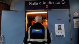 An Ikea employee enters the courtroom of the Versailles' courthouse, outside Paris, Monday, March 22, 2021. Ikea's French subsidiary and several of its executives are set to go on trial Monday over accusations that they illegally spied on employees and customers. (AP Photo/Christophe Ena)