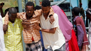 Somalis help a civilian who was wounded in suicide bomb attack at a military base in Mogadishu, Somalia, Tuesday, June 15, 2021 Police in Somalia say at least 15 people were killed and more than 20 others wounded when a suicide bomber attacked a military training center in the capital, Mogadishu, on Tuesday. (AP Photo/Farah Abdi Warsameh)